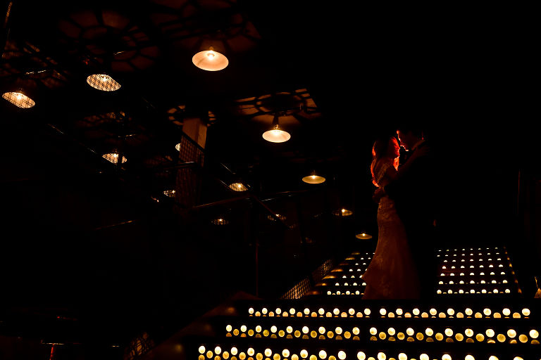 bride and groom dramatic lighting on staircase at wedding reception party photography by Candice C. Cusic