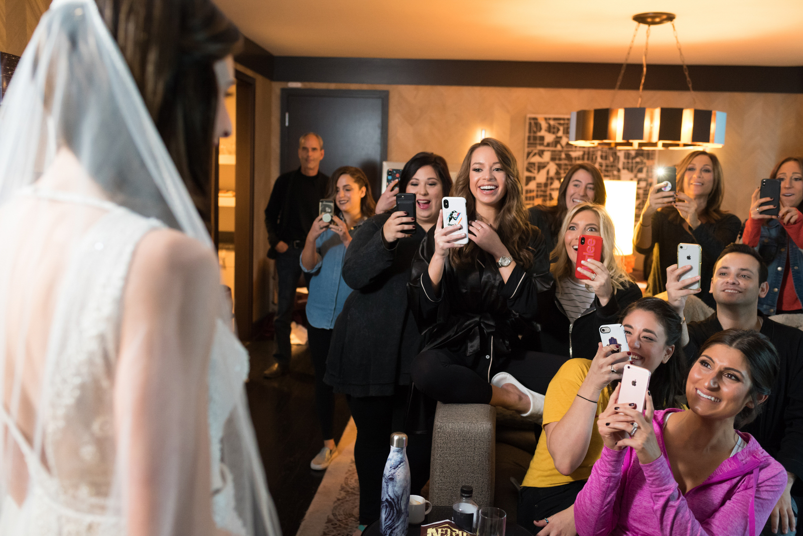 Wedding party and supportive family photographing bride Elana with wave of iphones. Photographed by Candice Cusic
