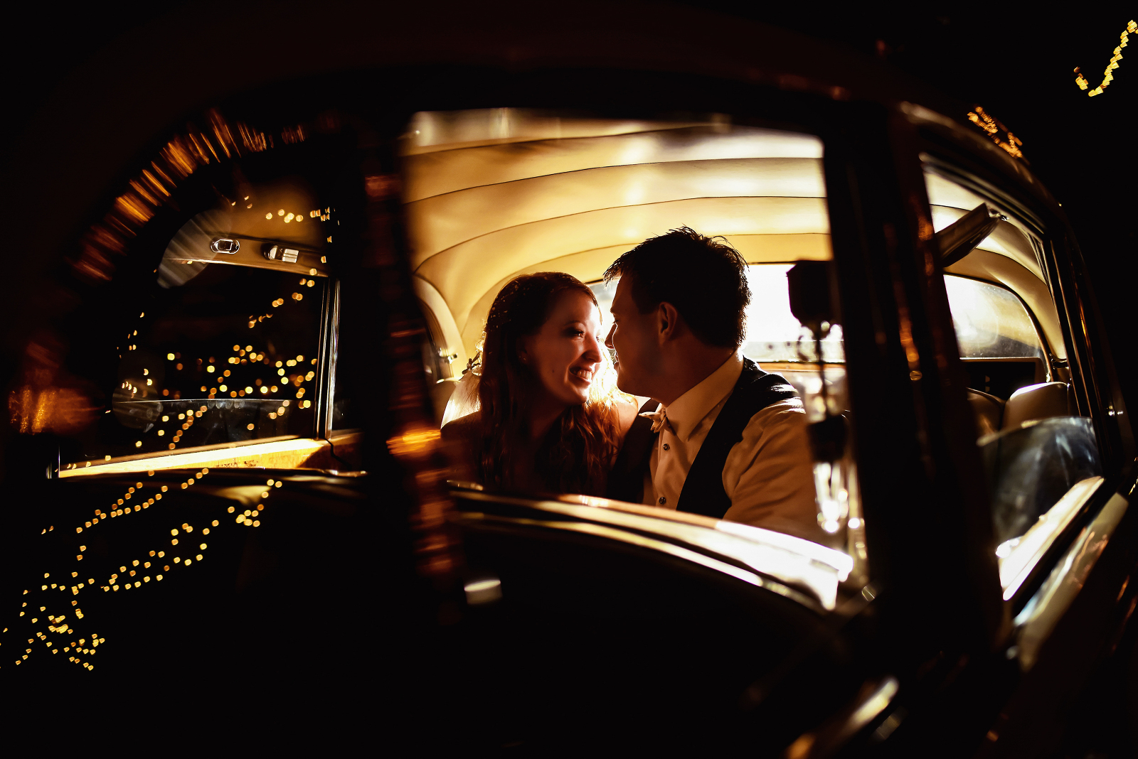 Bride and groom share a tender moment in a car. Photographed by Candice Cusic