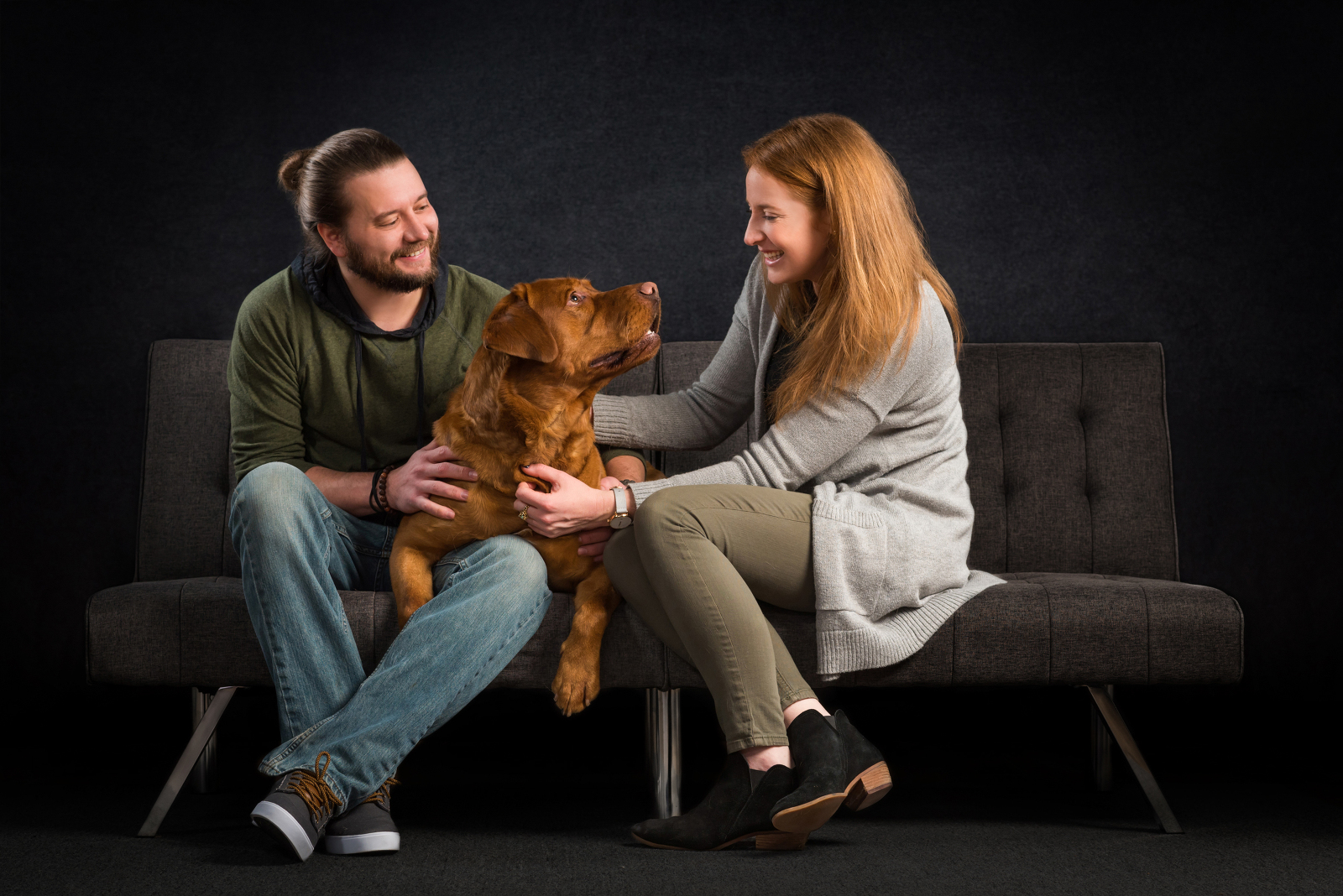 Pet parents of dog Nershi cozying up together on a couch during their photoshoot. Photographed by Candice Cusic